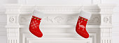Two red christmas stockings hanging on carved marble stone fireplace 3d rendering