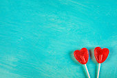 Two Red Heart Shape Candy Lollipops on Sticks on Turquoise Background Corner Position. Valentine Romantic Love Greeting Card Banner Poster with Copy Space. Creative Elegant Minimalist Style