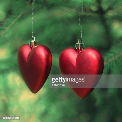 Dois vermelho corações pendurado em uma árvore de Natal : Foto de stock