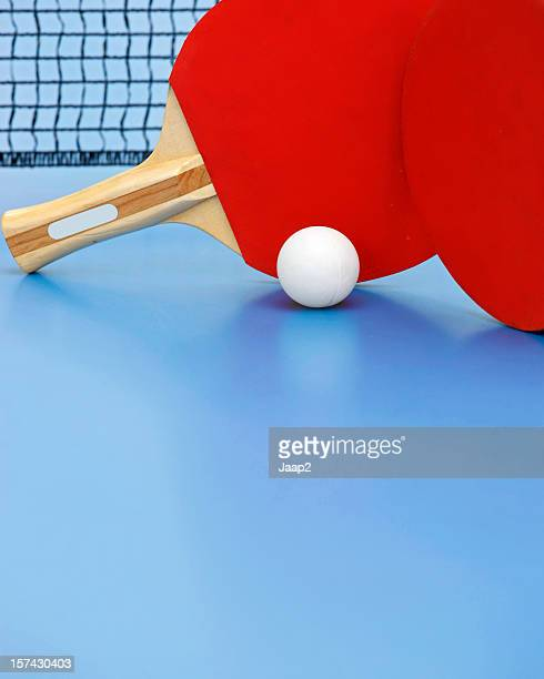 Two red ping-pong rackets and white ball on blue table