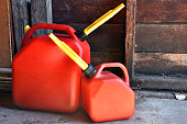 An image of two red plastic gas canisters.