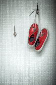 Two red sneakers hanging on peg