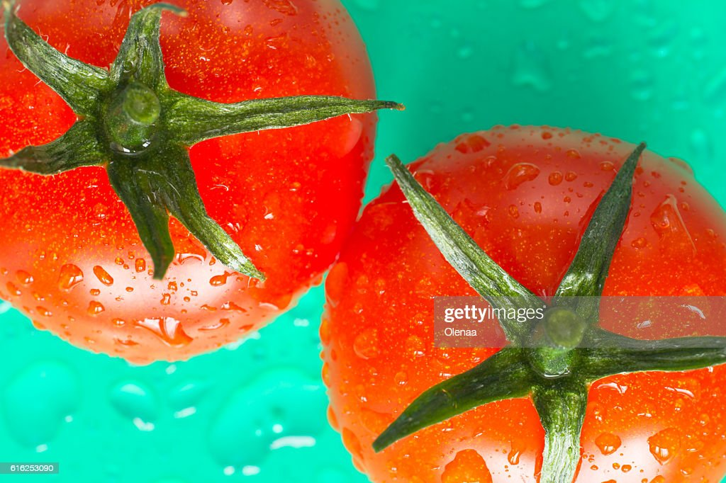 Two red tomatoes with green leaves. Top view. Green background : Foto de stock