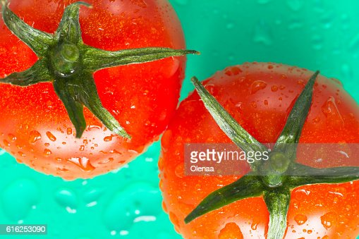 Two red tomatoes with green leaves. Top view. Green background : Stock Photo