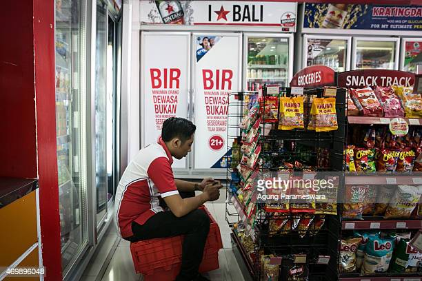 Two refrigerators that contain beer which are covered with a white banner are seen at Circle K while the worker of Circle K sits and holds his...