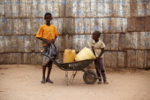 Two refugee boys push a wheelbarrow of water containers past a wall made from used USAID tins in the Dagahaley refugee camp which makes up part of...