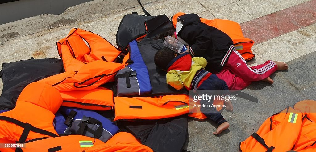 Two refugees children sleep on life vests after they were captured by coast guard while trying to pass illegally to Chios of Greek from Cesme in Izmir, Turkey on May 24, 2016. Turkish coast guard captured approximately 42 refugees after the operation.
