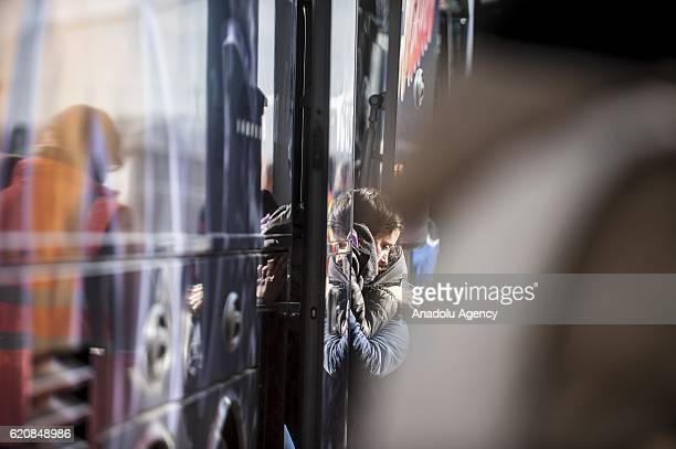Two refugees get a hug before climbing into a bus afterleaving the 'Jules Ferry' center reception in Calais on November 3 2016 Over 350 women and...