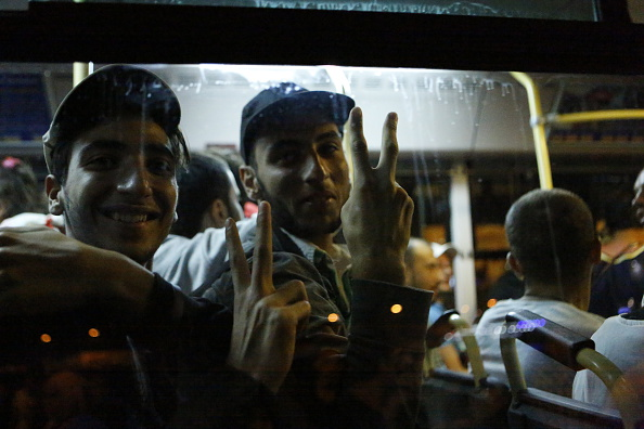 Two refugees make victory signs through the window of the...