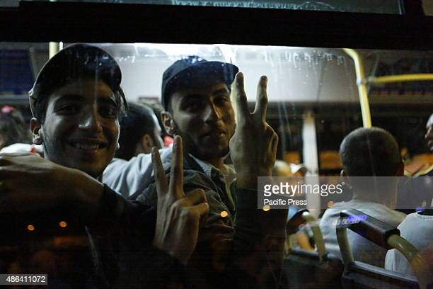 HARBOUR PIRAEUS ATTICA GREECE Two refugees make victory signs through the window of the bus that will bring them to the train station of Piraeus...