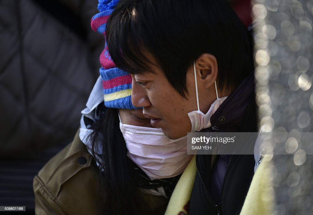Two relatives of trapped residents wait for information at the Wei-kuan apartment complex on the second day of search and rescue operations following a 6.4 magnitude earthquake in southern Taiwan's city of Tainan on February 7, 2016. Rescuers searched through the night hoping to free residents trapped in buildings toppled by the deadly earthquake in Taiwan, as survivors recalled being plucked to safety from their ruined homes. AFP PHOTO / Sam Yeh / AFP / SAM YEH