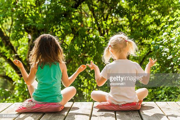 Two relaxed girls sitting on wooden terrace