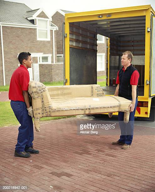 Two removal men carrying chaise longue covered in cardboard