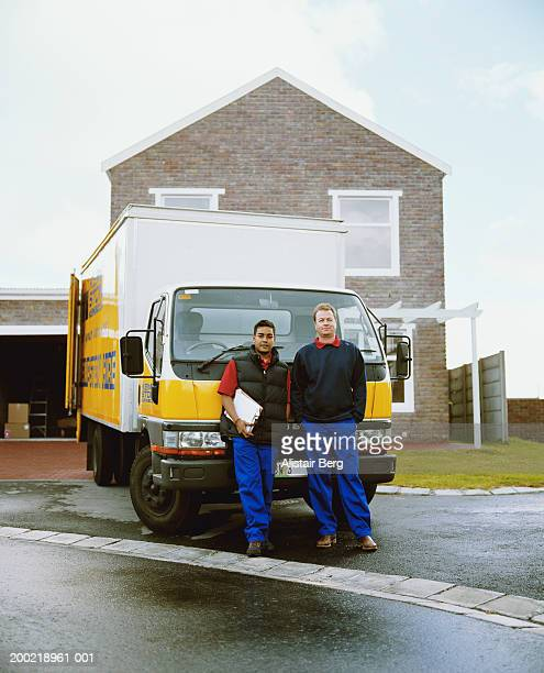 Two removal men standing in front of truck, smiling, portrait