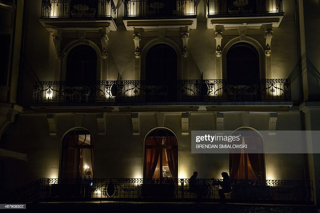 Two reporters sit on a patio while covering Iran nuclear program talks at the Beau Rivage Palace Hotel March 28 2015 in Lausanne Switzerland Tortuous...