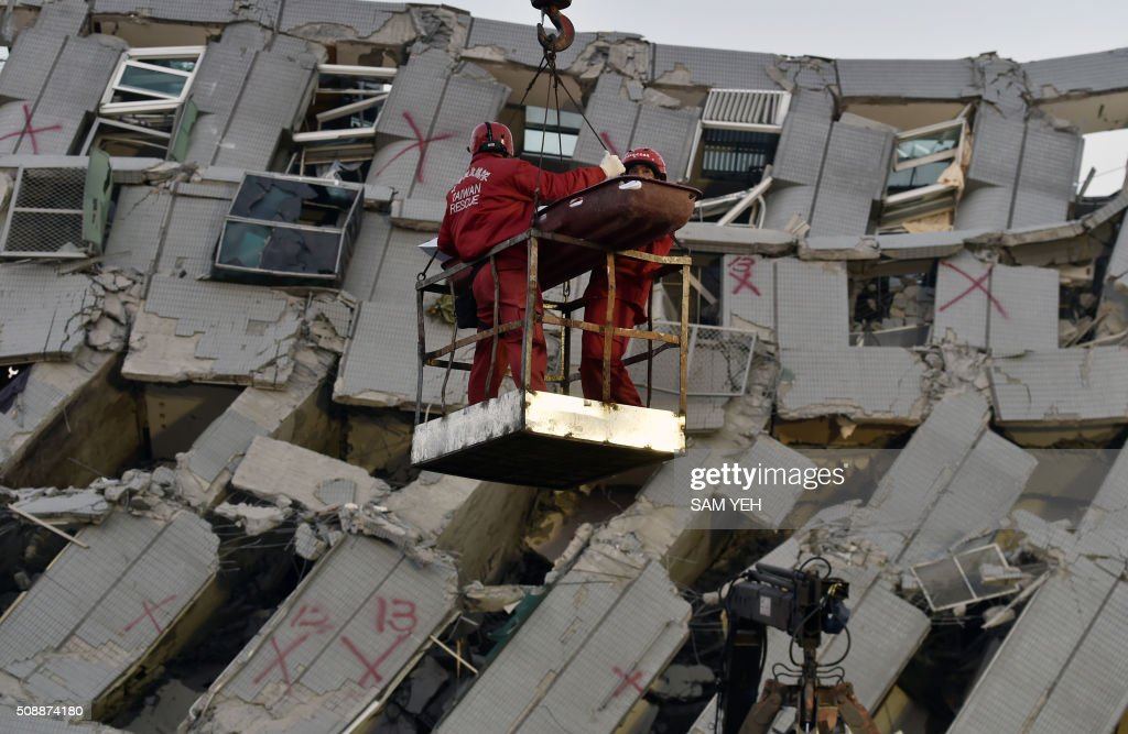 Two rescue workers bring down a victim from the collapsed Wei Kuan complex building in Tainan, southern Taiwan, on February 7, 2016, following a strong 6.4-magnitude earthquake that struck early on February 6. Rescuers raced on February 7 to free more than 120 people buried under the rubble of an apartment complex felled by an earthquake in southern Taiwan that left 24 confirmed dead, as an investigation began into the collapse. AFP PHOTO / Sam Yeh / AFP / SAM YEH