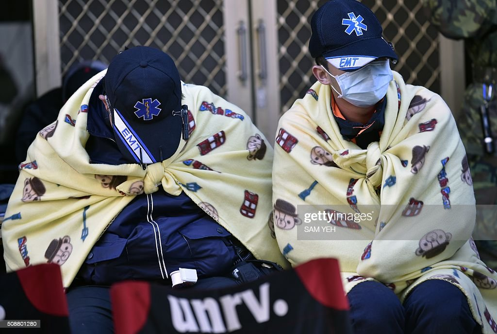 Two rescue workers rest after search operations continued all night at the Wei-kuan apartment complex following a 6.4 magnitude earthquake in southern Taiwan's city of Tainan on February 7, 2016. Rescuers searched through the night hoping to free residents trapped in buildings toppled by the deadly earthquake in Taiwan, as survivors recalled being plucked to safety from their ruined homes. AFP PHOTO / Sam Yeh / AFP / SAM YEH