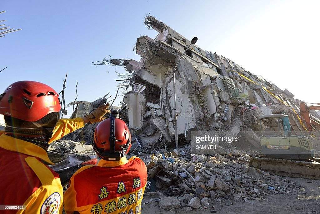 Two rescue workers stand next to the remains of the Wei-Kuan complex which collapsed in the 6.4 magnitude earthquake, in the southern Taiwanese city of Tainan on February 8, 2016. Two survivors were on February 8 rescued from the rubble of an apartment complex in Taiwan felled by an earthquake, after being trapped for more than 50 hours. AFP PHOTO / Sam Yeh / AFP / SAM YEH