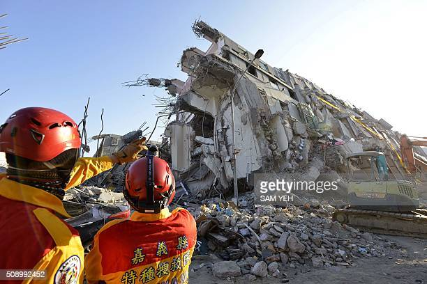 Two rescue workers stand next to the remains of the WeiKuan complex which collapsed in the 64 magnitude earthquake in the southern Taiwanese city of...