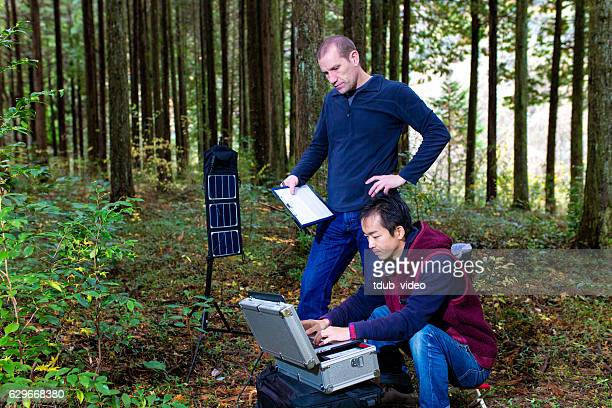 Two researchers in the forest with a solar powered laboratory