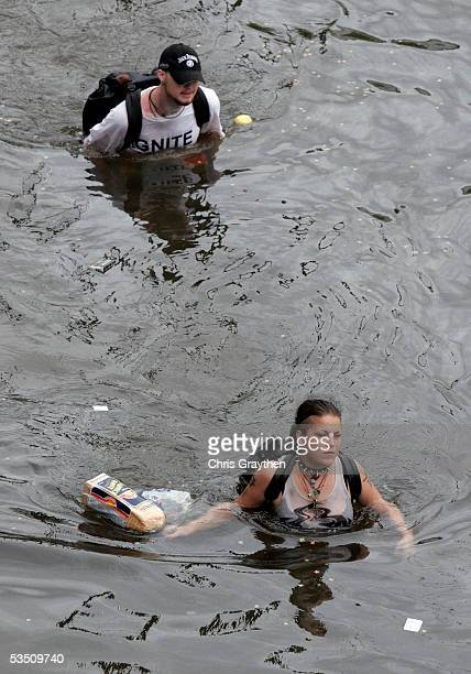 Two residents wade through chest deep water after finding bread and soda from a local grocery store after Hurricane Katrina came through the area on...