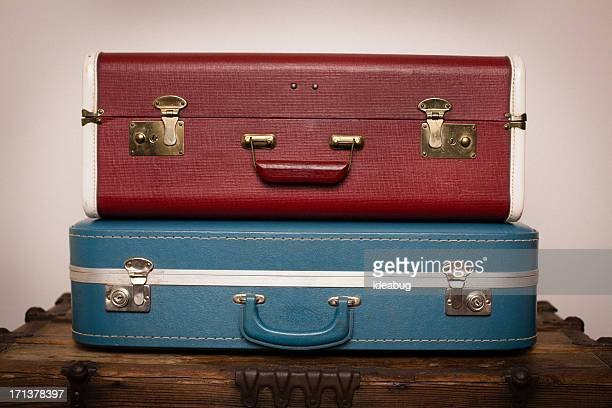 Two Retro Suitcases Stacked on Wood Trunk