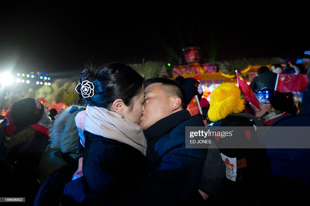 Two revellers kiss each other as they celebrate the new year during a count-down event at the Summer Palace in Beijing on January 1, 2013. AFP PHOTO / Ed Jones