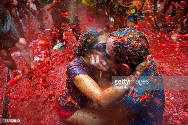 Two Revellers kiss each other covered in tomato pulp while participating the annual Tomatina festival on August 28 2013 in Bunol Spain An estimated...