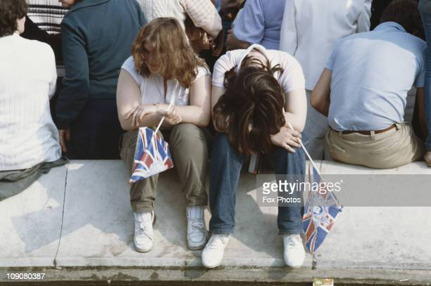 Two revellers look tired as they rest on the pavement during celebrations on the day of Prince Charles' wedding to Lady Diana Spencer London 29th...