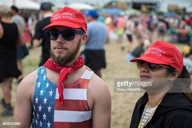 Two revellers mock President Donald Trump by jokingly wearing 'Make America Great Again' hats near the Pyramid stage at Glastonbury Festival Site on...