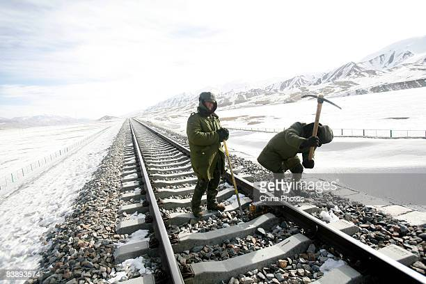 Two road workers carry out track maintenance along a line segment of the QinghaiTibet railway on December 2 2008 in Haixi Mongol and Tibetan...