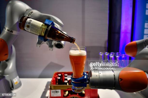 Two robotic arms by Industrial robot manufacturer Kuka pour a beer for guests attending the Summit of the Business20 in Berlin on May 2 2017 The B20...