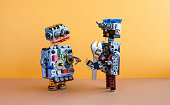 Two robots communication, machine learning concept. Robotic characters, adjustable wrench spanner. Yellow wall, brown floor background