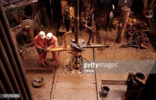 two roughnecks working on oil rig platform drill floor