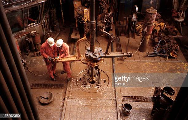 two roughnecks working on oil rig platform drill floor