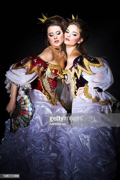 Two Royal Princesses Posing on Black Background