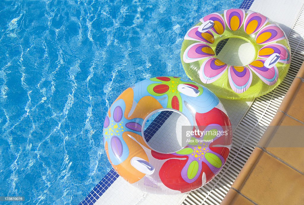 Two rubber rings on edge of swimming pool : Stock Photo