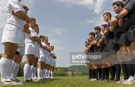 Two rugby teams standing on pitch facing each other, low angle view