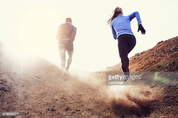 Two runners blazing a trail up a rocky hilly path