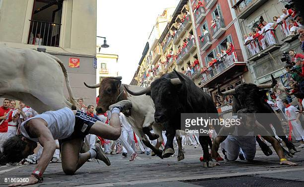Two runners fall in front of charging fighting bulls at the Mercaderes curve during the third San Fermin running of the bulls on July 9 2008 in...