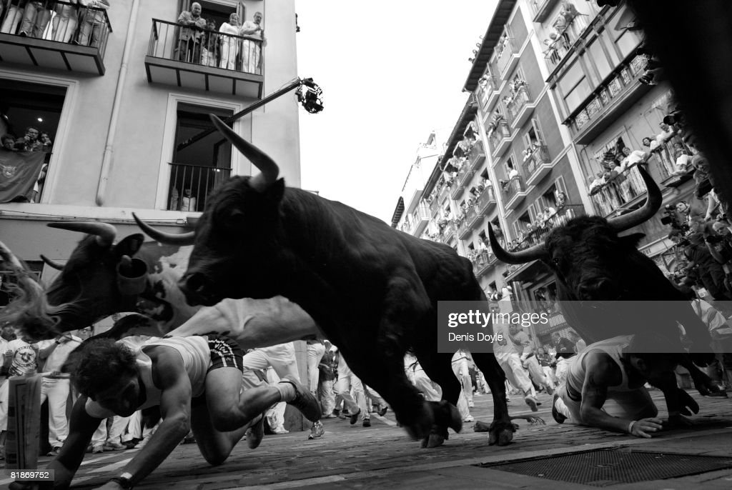 Two runners fall in front of charging fighting bulls at the Mercaderes curve during the third San Fermin running of the bulls on July 9, 2008 in Pamplona, Spain. Fighting bulls are run through the historic heart of Pamplona for eight days in this fiesta made famous by the 1926 novel of U.S. writer Ernest Hemmingway called 'The Sun Also Rises'.