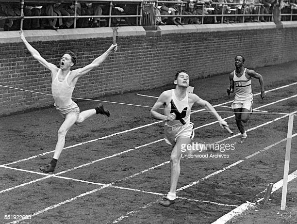 Two runners in the relay event cross the finish line in a dead heat at the Penn Relays Carnival Philadelphia Pennsylvania 1946