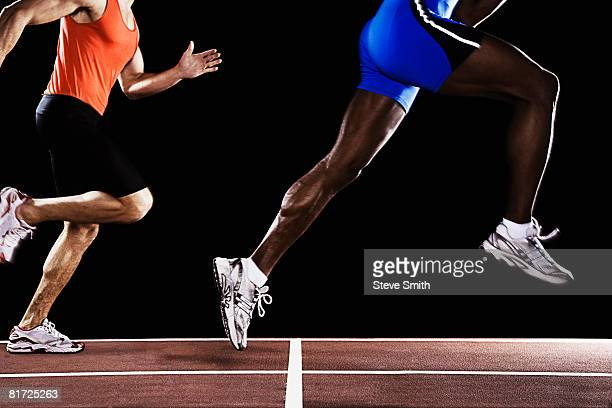 Two runners on race track with one jumping up in air
