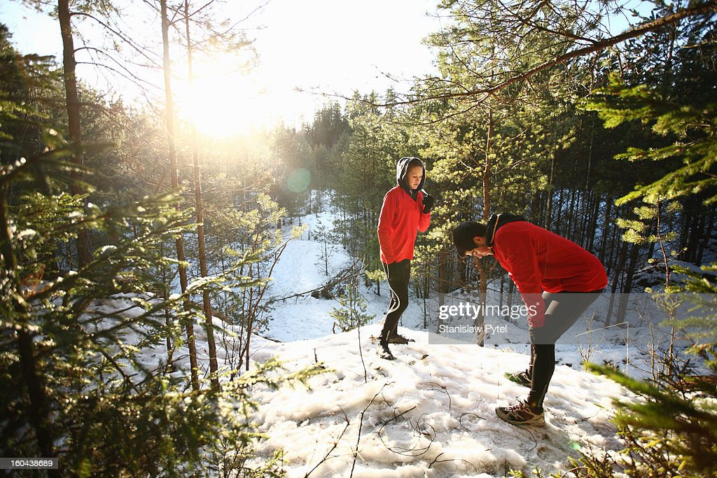 Two runners resting in snowy forest : Stock Photo