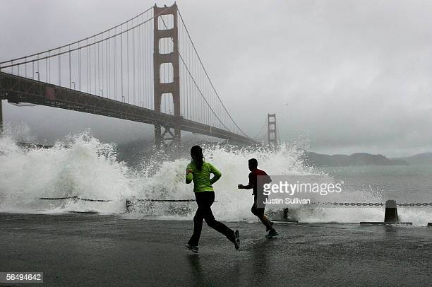Two runners watch as a waves crash against the rocks at Fort Point near the Golden Gate Bridge December 28 2005 in San Francisco A series of wet...