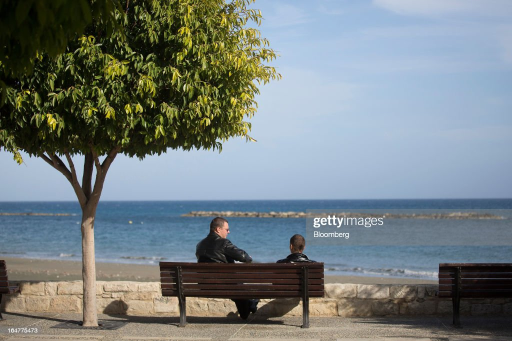Two Russian men sit and talk on a bench by the Mediterranean sea in Limassol, Cyprus, on Wednesday, March 27, 2013. The ECB said on March 25 it won't stop the Cypriot central bank from providing the island's banking sector with emergency funding. Photographer: Simon Dawson/Bloomberg via Getty Images