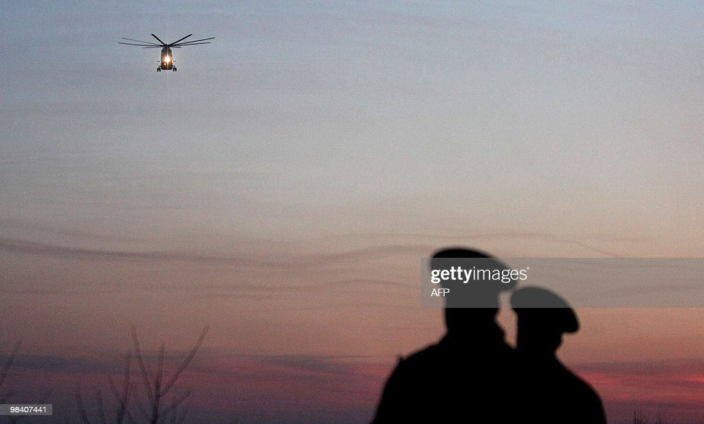 Two Russian policemen look at a helicopter carrying dead bodies of a Polish government Tupolev Tu154 aircraft crash near Smolensk airport on April 10...