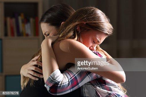 Dos adolescentes tristes abrazar en el dormitorio : Foto de stock