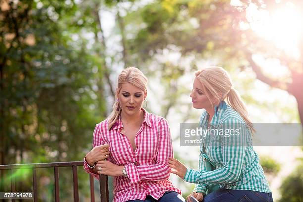 Two sad young beautiful girls portrait outdoors