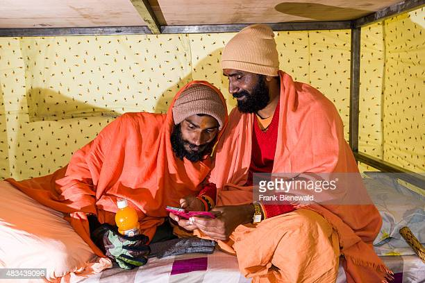 KEDARNATH UTTARAKHAND INDIA Two Sadhus holy men are playing with a smartphone in a tent
